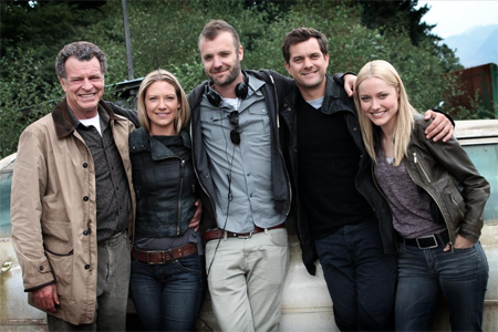 a behind the scenes photo of the Fringe cast with a director